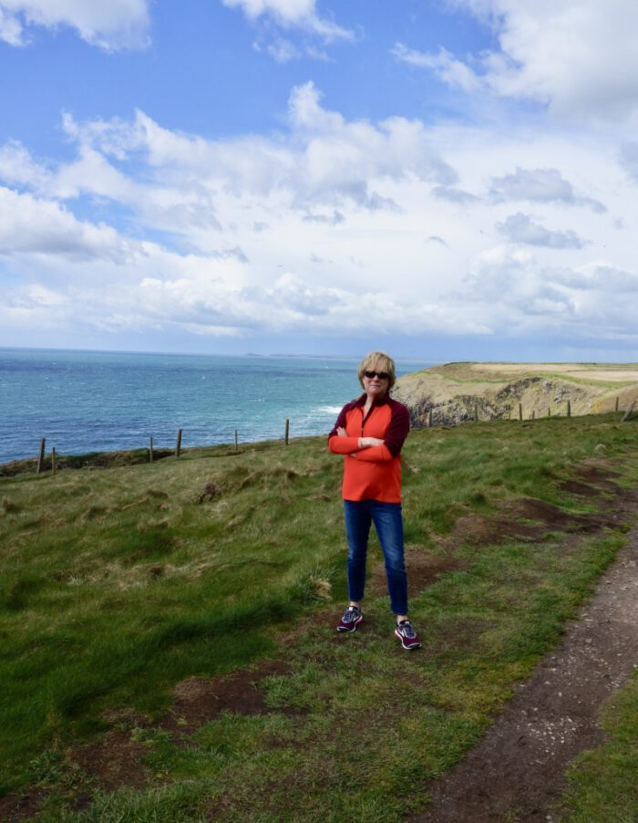 Carla on the cliffs in Ardmore Ireland while wearing an orange jacket